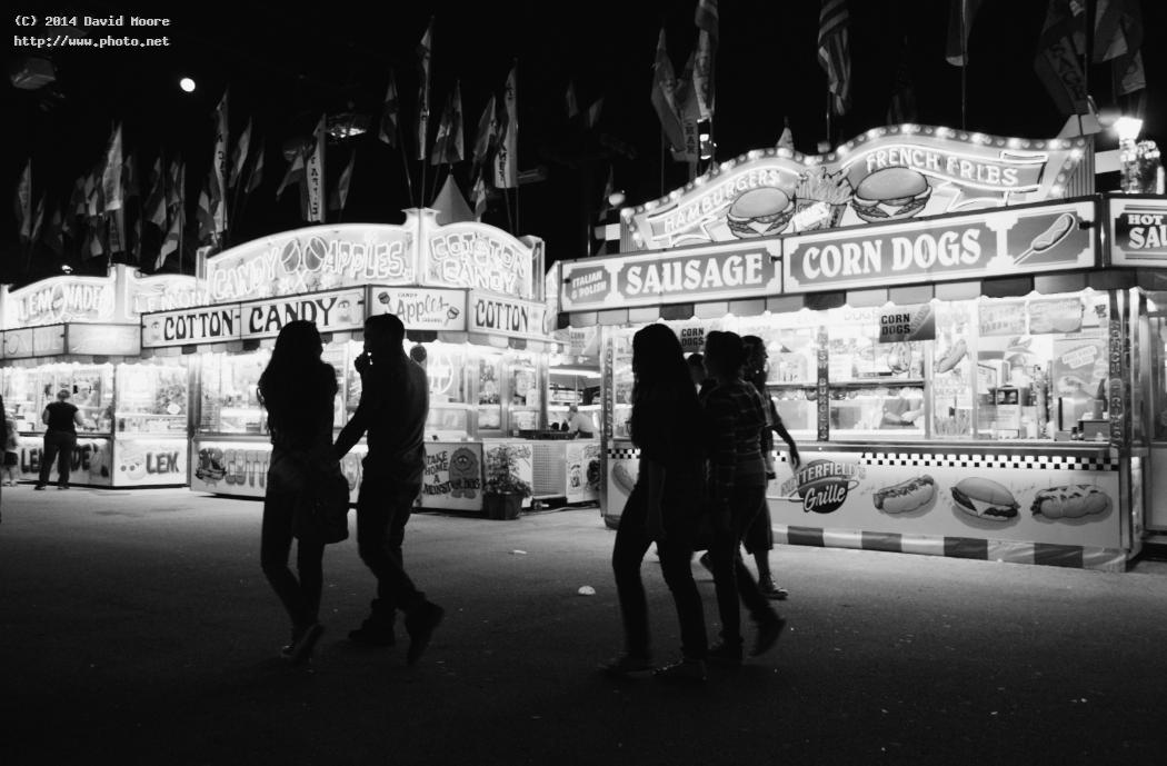 fairgoers on the midway food night fair bw seeking critique moore david